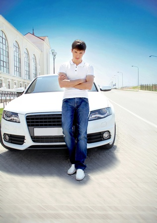 Handsome man casually leaning against the white car, road outdoors