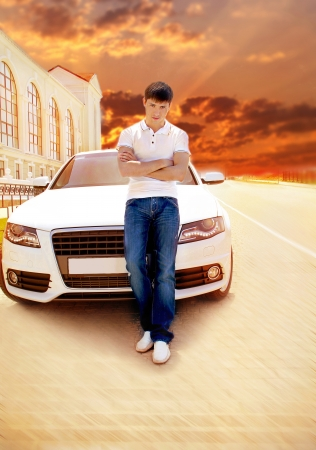Handsome man casually leaning against the white car at sunset, road outdoors portrait photo
