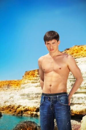 shirtless male: Portrait of Sexy young fit  man on the beach, blue sky