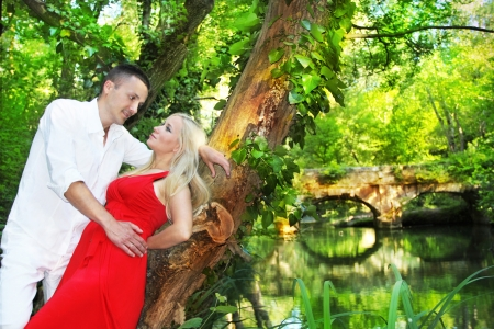 Loving couple leaning against the tree on green park, enjoying their spring holiday together Stock Photo - 13703059