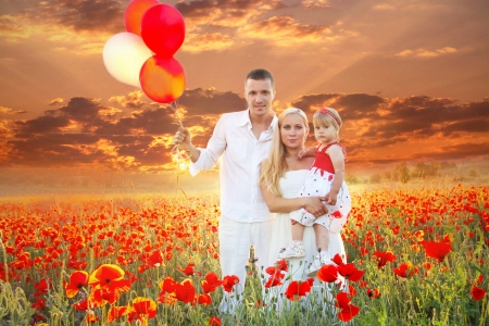 Happy family on  Field of poppies spring flowers, sunset outdoors photo