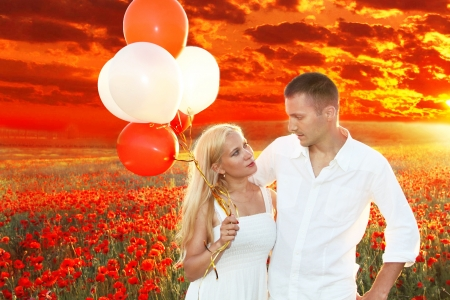 Happy couple embracing over poppies field and sunset, holding bunch of balloons photo