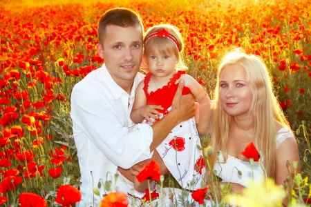 Happy family on poppies flowers field, sunset outdoors Stock Photo - 13703056
