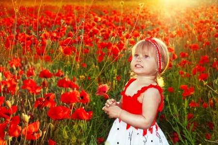 emotional freedom: Happy smiling little fun girl in red poppies field, sunset outdoors portrait Stock Photo