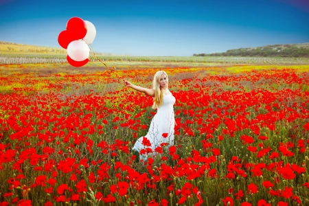 Portrait of romantic woman in poppy field in white dress