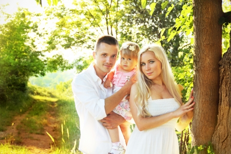 Happy young family with pretty child posing  on green park countryside, outdoors photo
