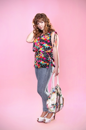 beautiful girl with bag is in style of pinup, over pink photo