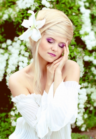 Young pretty woman with beautiful blond hairs and multicolor makeup, outdoors portrait