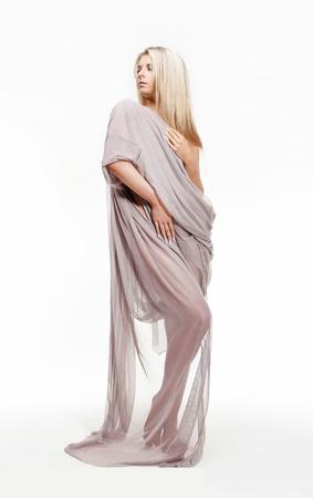 windblown: Portrait of beautiful sexy young woman in drapery dress Stock Photo