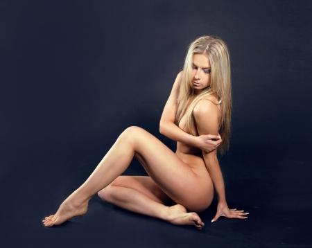 modelle nude: Foto di moda della bella donna nuda con il corpo sexy tan su sfondo scuro