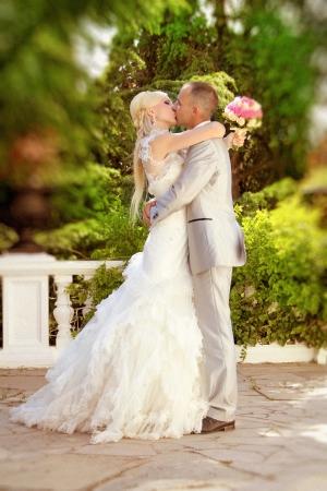 love kissing: Groom kissing bride on their wedding walk Stock Photo
