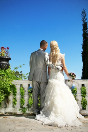 Beautiful bride and groom leaning over the railing for a quiet moment of happiness photo