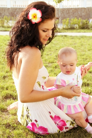 Beautiful young mother daughter relaxing sitting on green grass background, summer meadow  photo