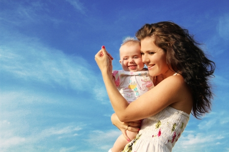 happy mother with baby over blue sky photo