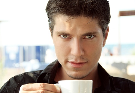Elegant young handsome man with cup photo