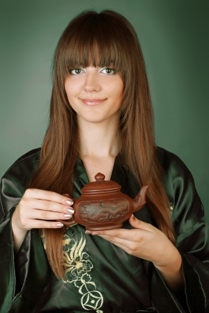 Green Tea ceremony happy woman with teapot on hands  photo