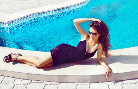 Fashion woman sunbathing near swimming pool, outdoors photo