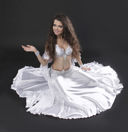 Beautiful exotic belly dancer woman over black background photo