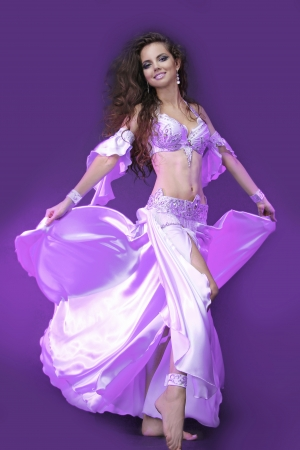 belly dancer in violet costume, active young woman