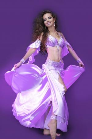buikdansen: buikdanseres in violet kostuum, actieve jonge vrouw