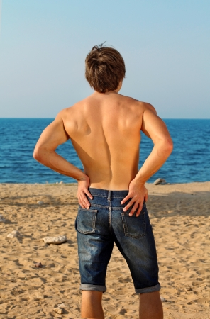 Fit Man in jeans looking away on ocean photo