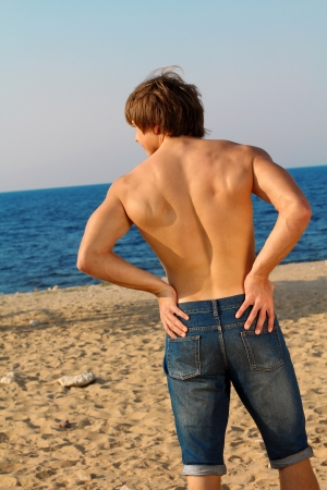 Resting handsome muscular man in jeans on beach photo