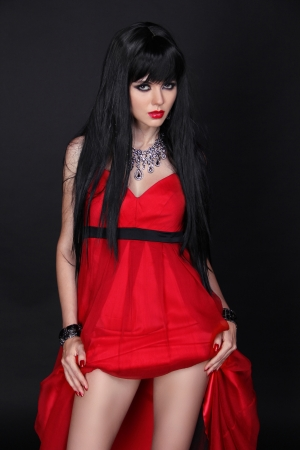 Beautiful brunette girl in red dress isolated on black Stock Photo - 14886684