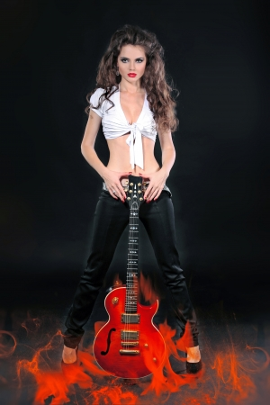 Female rock star with guitar in fire over black background photo