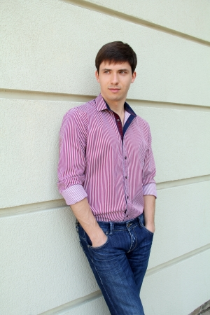 warm shirt: Handsome man casually leaning against the wall