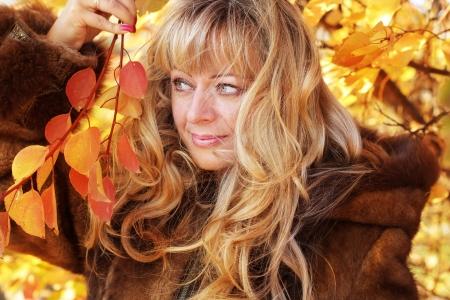 Belle femme blonde âgée moyenne dans des feuilles d'automne