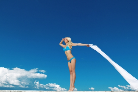 Beautiful young woman over the blue sky with white tissue photo