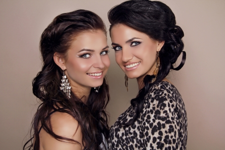 Two attractive smiling girls friends, sisters women studio shot photo