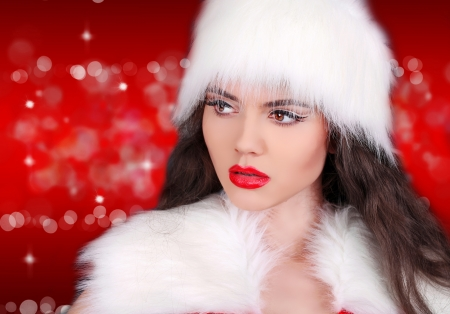 Santa girl with red lips looking away on red bokeh abstract  photo