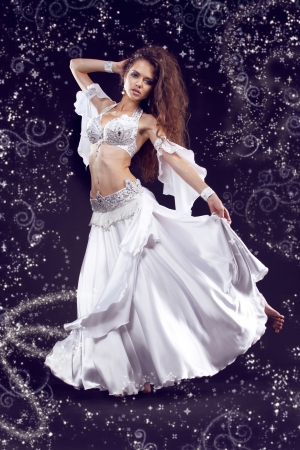 Beautiful exotic belly dancer woman in white costume, girl with smart fair hair   photo