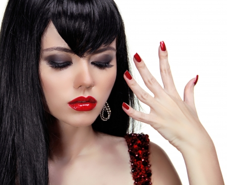 Sensual brunette woman with red lips and nails manicure, silky hair