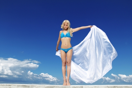 Beautiful Girl With White Scarf over blue sky. Travel and Vacation. Freedom Concept photo