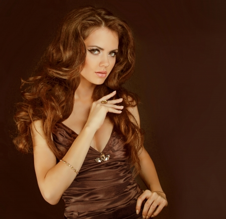 Fashion lady, sensual brunette woman with shiny curly silky hair in elegant dress photo