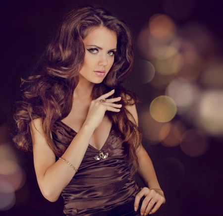 Fashion lady, sensual brunette woman with shiny curly silky hair in elegant dress Stock Photo