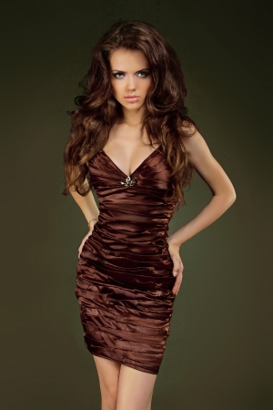 sexy black dress: Beautiful woman with curly hair posing in elegant dress. Jewelry and Beauty.   Stock Photo