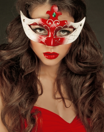 Beautiful Girl in Carnival mask with long curly hair. Masquerade Holidays  photo