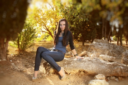 Full length portrait of teen young woman sitting, outdoors photo