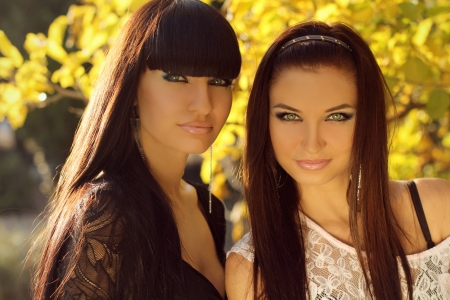 two people only: Two brunette women outdoors portrait. Soft sunny colors.