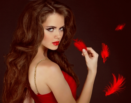 Woman with beauty long curly brown hair and red lips. Fashion woman Portrait.