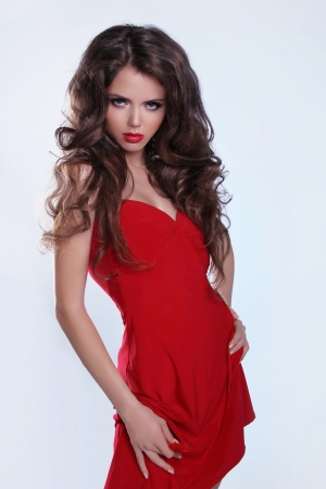 Woman with beauty long brown hair posing in red dress, posing at studio Stock Photo - 16018269