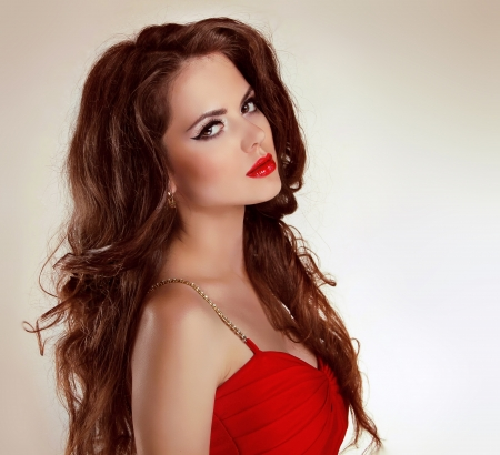 Beautiful brunette girl with curly hairs in red dress