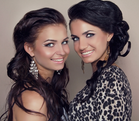 Two attractive smiling girls friends, sisters women studio shot Stock Photo - 16143305