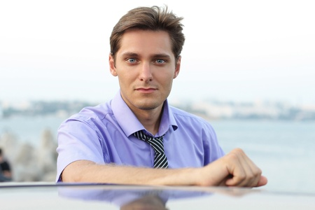 Elegant young handsome man on car background