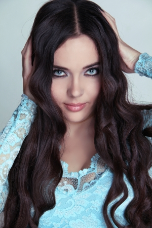Beautiful Brunette Girl. Healthy Long Curly Hair. Lady in blue dress Stock Photo - 16664729