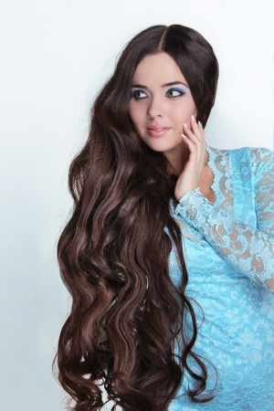 brown hair blue eyes: Beautiful Brunette Girl. Healthy Long Curly Hair. Lady in blue dress looking away