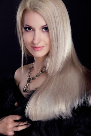 Blond woman with Healthy Long Hair isolated on black background photo